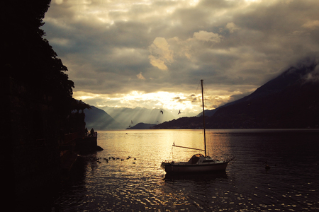 Silver linings in Lake Como at the sunset. Yacht. Boat on the water. Sunset view. Lombardy. Varenna, Italy.