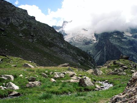 High mountains through the green valley. View of Distant Peaks. Vintage photo. Stones and grasses. Uzunkol Valley, Caucasus Mountains, Karachay-Cherkessia, Russia.