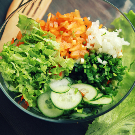 Glass bowl with cut vegetables for a salad.