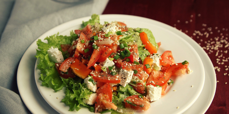 Tomato salad on the white plate. European cuisine. Close up. Colorful salad with vegetables and cottage cheese. Lacto vegetarian dish. Tomatoes, celery, leafy greens and sesame seeds. Imagens