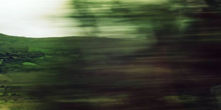 Defocused trees viewed through a car windscreen. Toned filter photo. Blurred action from car at high speed. Vague view through moving car window. Ring of Kerry, Ireland. 免版税图像