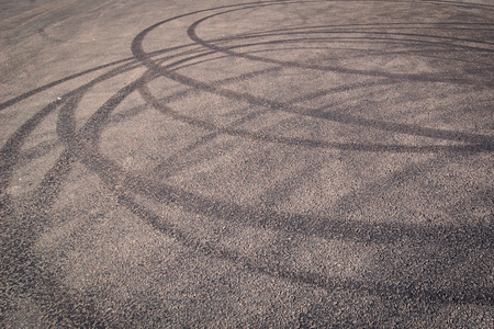 Urban background with tire tracks on the asphalt. Tone dimage. Abstract road backdrop with tyre marks on gray surface. Maneuverability test. Urban track marks. Stock Photo