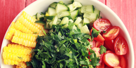 White plate with cut vegetables for a vegan salad on the red wooden table. Colorful photo. Corn, cherry tomatoes, bell pepper, onion, cucumber and garden herbs. Wide photo. Top view.