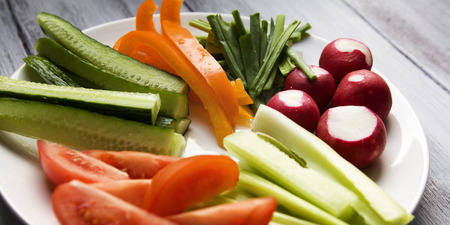 White plate with vegetables for a vegetarian salad. Radishes, tomatoes, celery, bell pepper, onion and cucumber. White wooden kitchen table. Close up. Wide photo.