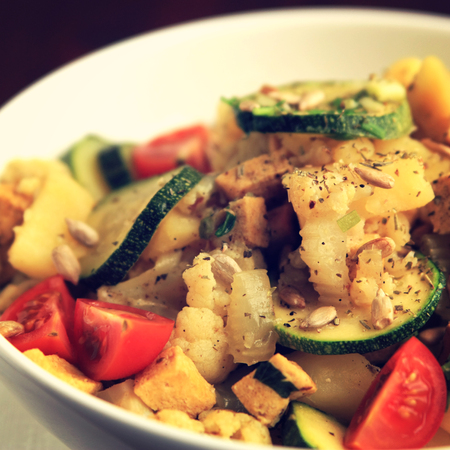 Vegetable stew with tofu, cauliflower and zucchini topped with sunflower seeds. European cuisine. Healthy vegan lunch in the bowl. Main course. Vegetarian dish. Toned square photo.