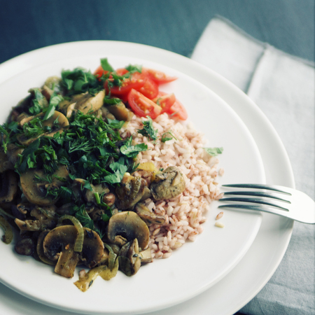 Red rice with mushrooms and cherry tomatoes. Vegan dish. European cuisine. Simple healthy lunch. Vegetarian rice dish on the white plate. Close up. Toned photo.