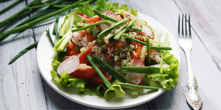 Spring Vegetable Salad on the white plate. Radish, tomato, celery and cucumber. Topped with sesame seeds. Vegetarian dish on the white wooden table. Close up. Wide photo. 免版税图像