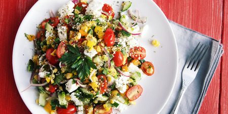 Colorful vegetable mix. Simple low calories salad. Cherry tomatoes, sweet corn, cucumber, bell pepper and cottage cheese. Weight loss dish. European cuisine. Top view. 免版税图像