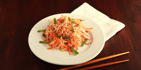 Vegan salad with carrot and radish. Asian cuisine. Healthy vegetarian appetizer on the round plate. Side dish. Simple low calories lunch. Wide photo.