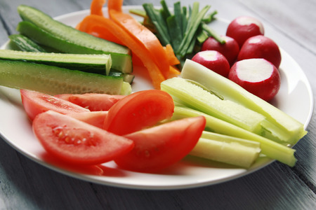 White plate with vegetables for a vegetarian salad. Radishes, tomatoes, celery, bell pepper, onion and cucumber. White wooden kitchen table. Close up. Banque d'images