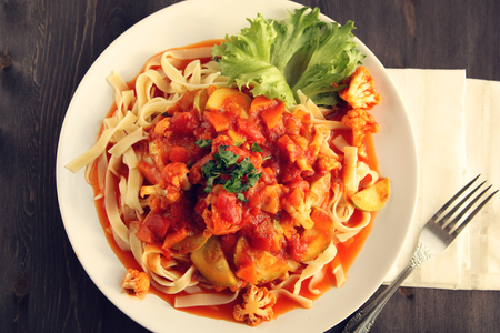 Ribbon pasta with Arrabiata sauce. Close up. Mediterranean dish. Tagliolini pasta with vegetables. Cauliflower, courgette and tomato stew. Italian cuisine. Vegan and vegetarian. Top view. 免版税图像