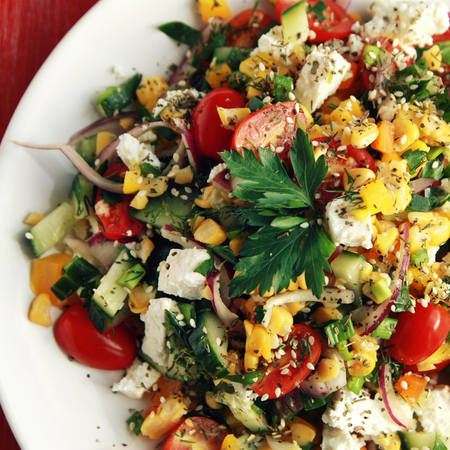 Colorful vegetable mix. Simple low calories salad. Cherry tomatoes, sweet corn, cucumber, bell pepper and cottage cheese. Weight loss dish. European cuisine. Top view. Toned photo.