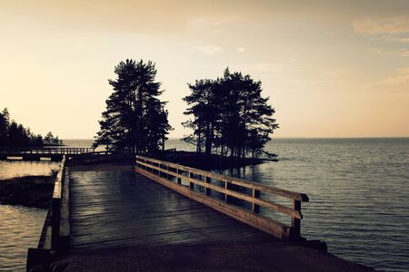 Pedestrian timber bridge on the Valaam island. Cloudy summer evening. Sunset. Rainy day. Russian north. Across the water. Valaam island, Karelia, Russia. 免版税图像