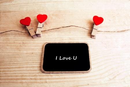 i love u: Un tableau noir avec les mots I Love U et une cha?ne de coeurs rouges Banque d'images