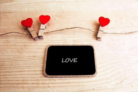 A black board with words  LOVE  and a string of red hearts