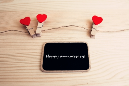 A black board with words  happy anniversary  and a string of red hearts