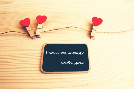 A black board with words  I will be always with you  and a string of red hearts