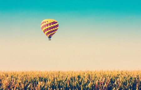 Hot air balloon flying over corn fields against blue sky in old style