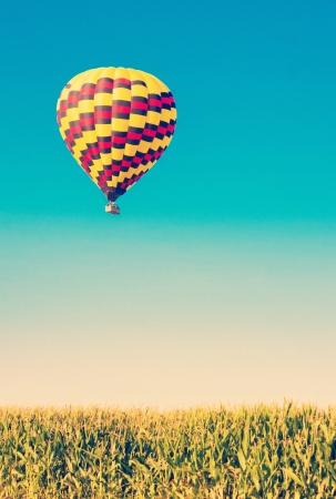 Heißluftballon fliegen über Maisfelder gegen den blauen Himmel im alten Stil Standard-Bild - 21167029