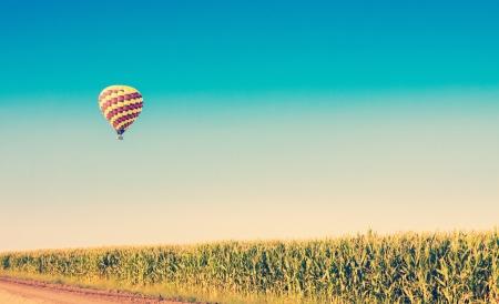 Heißluftballon fliegen über Maisfelder gegen den blauen Himmel im alten Stil Standard-Bild - 21167031