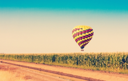 Hot air balloon flying over corn fields against blue sky in old style 版權商用圖片 - 21167032