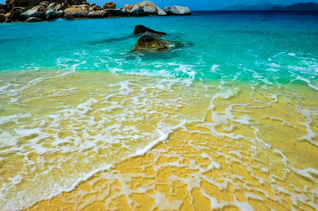 Beautiful view of Virgin Gorda's beach with the contrasting colors of the sand, the sky and the crystal clear water. The sea water is contrasting wiht the orange sand and the blue sky.