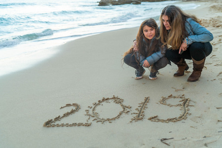 Mother and daughter looking at 2019 written on the sand