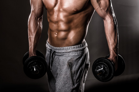 human arms: Beautiful male torso with weights Stock Photo