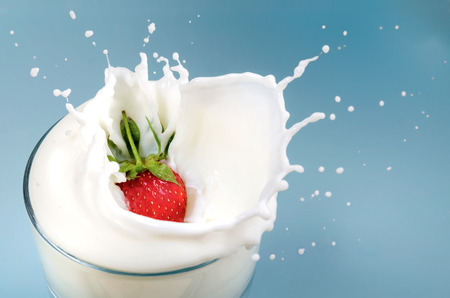 Strawberry Drops in Milk With Splash on Blue Background