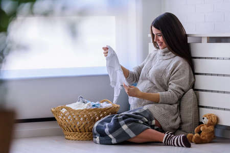 Beautiful young smiling pregnant woman preparing clothes for her baby.