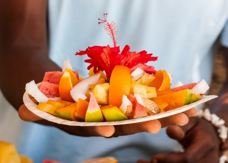 Local man holding a plate of tropical fruits