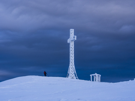 apennines: Hiker reaching the summit of Mount Catria cross in winter with snow, stormy sky, Apennines, Marche, Italy Stock Photo