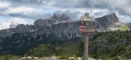 wooden trail sign: Wooden trail sign in the Dolomites with Croda da Lago mountain range, blue sky with clouds, Dolomites, Veneto, Italy