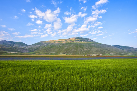 monti: Monte Vettore and Piano Grande at sunset, Summer day with blue sky with clouds, Monti Sibillini NP, Umbria, Italy Stock Photo
