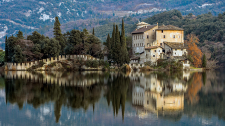 Panoramic view of historic Castle of Toblino and bridge reflecting on lake in countryside
