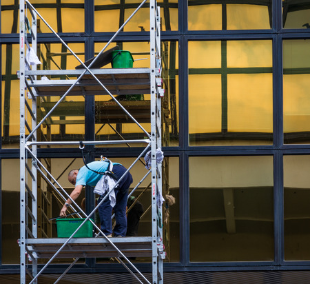 worker clean a window at the business center. Trento city. Italy