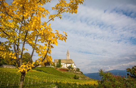 autumn view of the Church of the idyllic village of Cortaccia. Cortaccia extends on the sunny side of the wine road. South Tyrol, Italy. Stock Photo