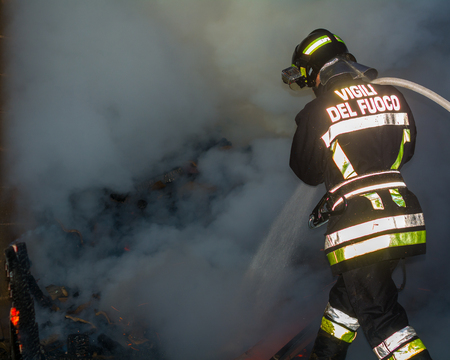 extinguishing: Fireman at work in to the fire