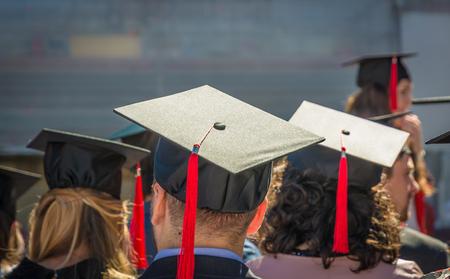 Back of graduates during the graduation ceremony. Close up at graduate cap. Education, People, Graduate concept Sajtókép