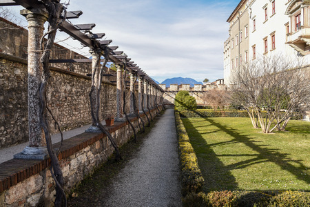 The outdoor gardens of the majestic Castle of Buonconsiglio at the heart of the city of Trento towers in Trentino Alto Adige, northern Italy.