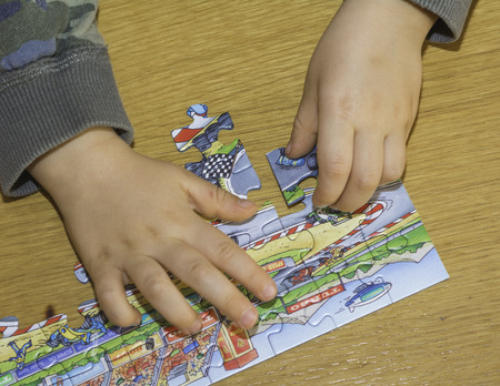 Baby hands assemble the puzzle on the table Imagens
