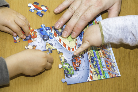 little kids playing with puzzles on wooden table together with parent, lifestyle people concept