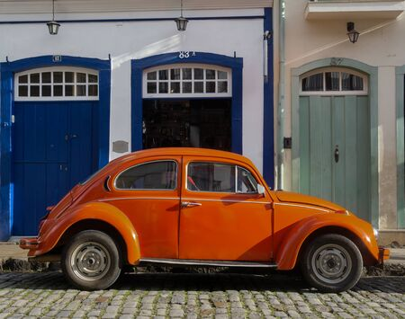 OURO PRETO, MINAS GERAIS, BRAZIL - DECEMBER 24, 2019: Orange retro car Volkswagen Beetle parked  on the street in the ancient city of Ouro Preto, Brazil. Volkswagen Type 1, best known as Beetle car is an economy car produced by Volkswagen from 1938 unti