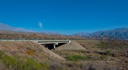 Long shot of Cacheuta Bridge in National route 7 toward the Chilean border  in Lujan de Cuyo, Mendoza, Argentina Stock Photo