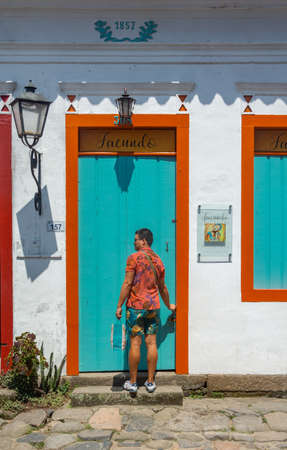 PARATY, RIO DE JANEIRO, BRAZIL - DECEMBER 28, 2019: a man unlocks the colorful building's door in the historic city of Paraty, Brazil. The preserved colonial center of the city was included on UNESCO World Heritage list in 2019.