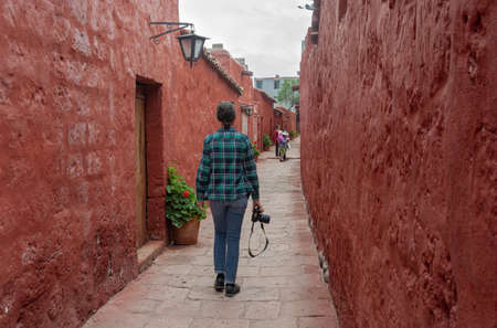 AREQUIPA, PERU - JANUARY 17, 2018: Unidentified tourist with a camera in her hands walks through narrow street in the Monastery of Santa Catalina, in Arequipa, Perú. This convent was founded in 1580.