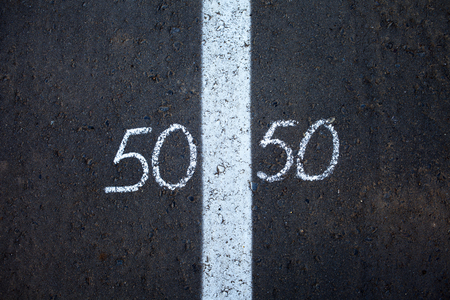 Symbol of gender equality 50/50 on asphalt
