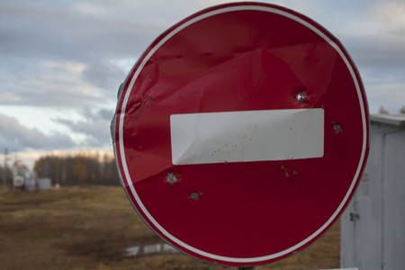 No entry road sign with bullet holes, target practice