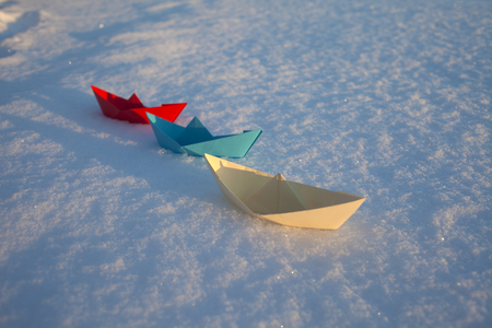 Red, blue and white paper boat in the snow. Winter Фото со стока
