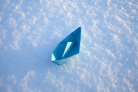 blue paper boat in the snow. Winter